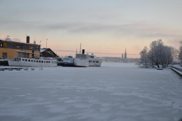 Det var riktigt kallt i morse, det fick bli en kortare promenad längs Söder mälarstrand i soluppgången. Pålsundskanalen är igenfrusen, under gryningshimmelns pastellfärger ligger Gamla stan som en suddig dröm.