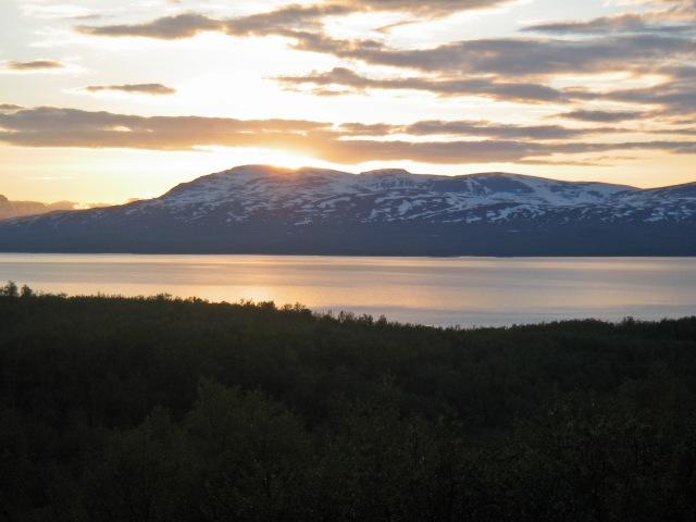 Svar: man ser solen vid midnatt! Den här bilden är tagen 14 juli 2006, klockan 00.01. Solen tittar fram bakom ett fjäll på nordsidan av Torne träsk. Ett moln dämpar ljuset från solen litegrann, och därmed går det att fotografera rakt mot solen.